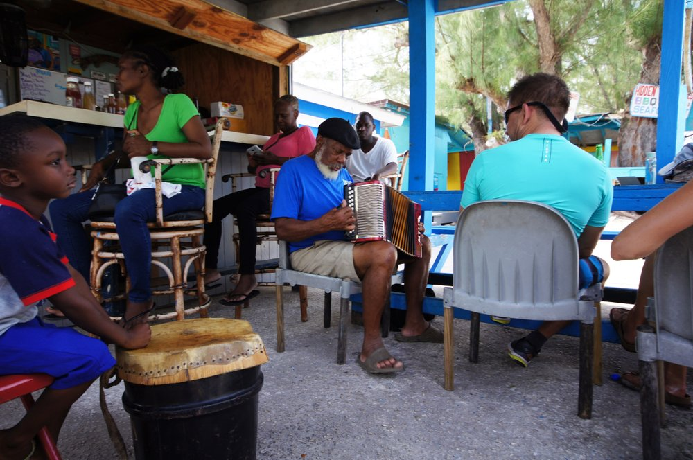 Pompei Johnson breaks out his accordion at CeeDee's, a restaurant in New Bight, Cat Island, Bahamas, while a local boy plays a goat-skin drum and tourists look on.