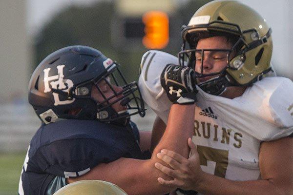 Jack Struebing (left) of Har-Ber blocks a Pulaski Academy defender during a game Friday, Aug. 24, 2018, in Springdale.