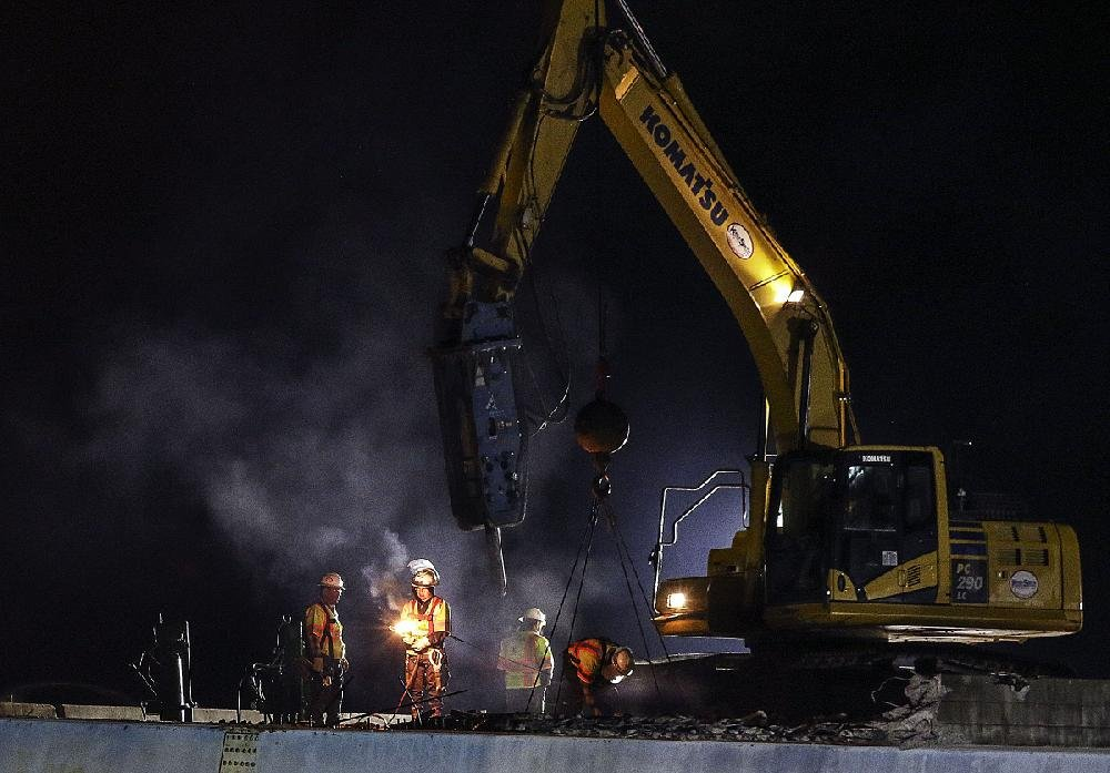 Construction workers demolish a bridge Friday night on Interstate 630 at Rodney Parham Road in Little Rock.