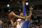 Florida guard KeVaughn Allen (5) shoots under pressure from Florida Gulf Coast forward Troy Baxter Jr. (1) in the first half of an NCAA college basketball game, part of the Orange Bowl Classic tournament, Saturday, Dec. 22, 2018, in Sunrise, Fla. (AP Photo/Joe Skipper)