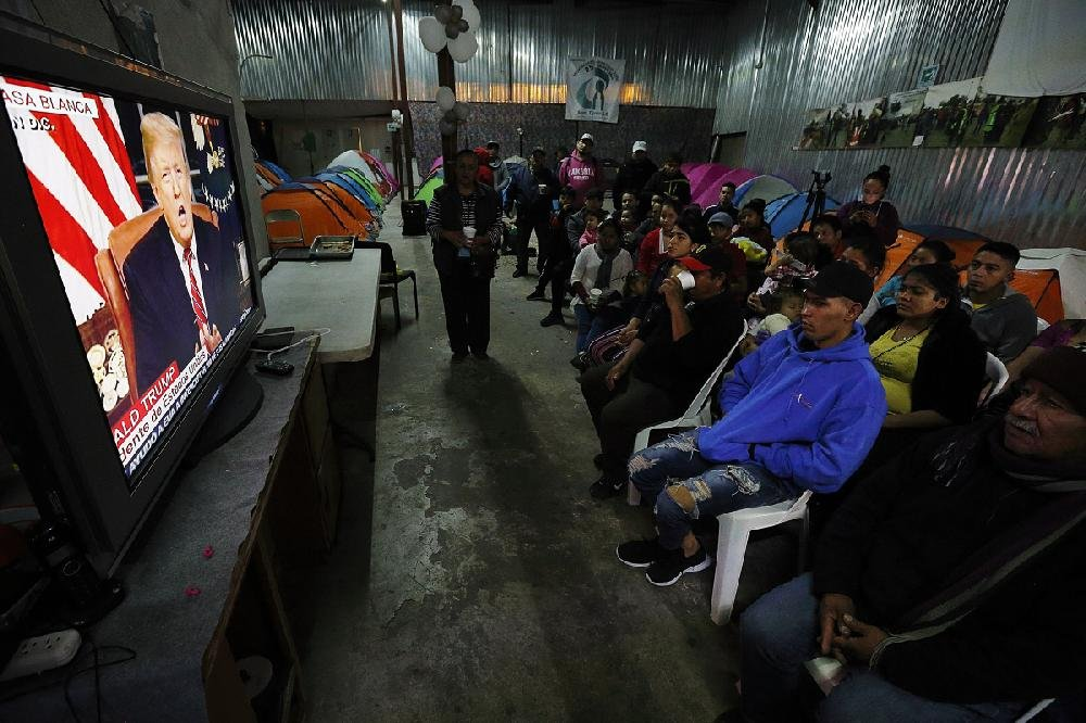 Migrants, mainly from Central America and Mexico, watch President Donald Trump's speech from a migrant shelter in the border city of Tijuana, Mexico.