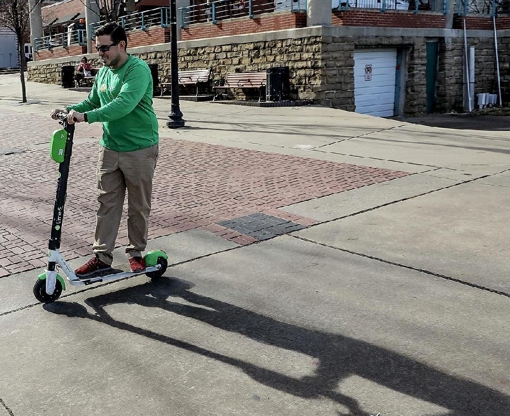 Lime representative Kris Alborz rides a rechargeable scooter Tuesday near the Riverfront Park Amphitheater in Little Rock.