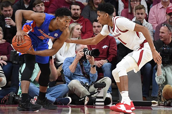 Florida senior KeVaughn Allen (left) is guarded by Arkansas freshman Isaiah Joe during a game Wednesday, Jan. 9, 2019, in Fayetteville.