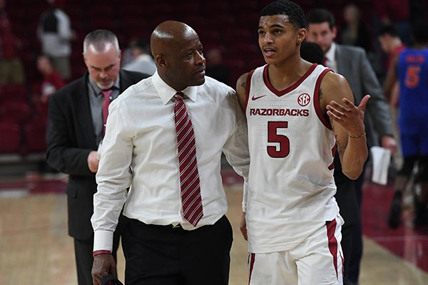 Arkansas coach Mike Anderson (left) walks off the floor with guard Jalen Harris (right) following a 57-51 loss to Florida on Wednesday, Jan. 9, 2019, in Fayetteville.