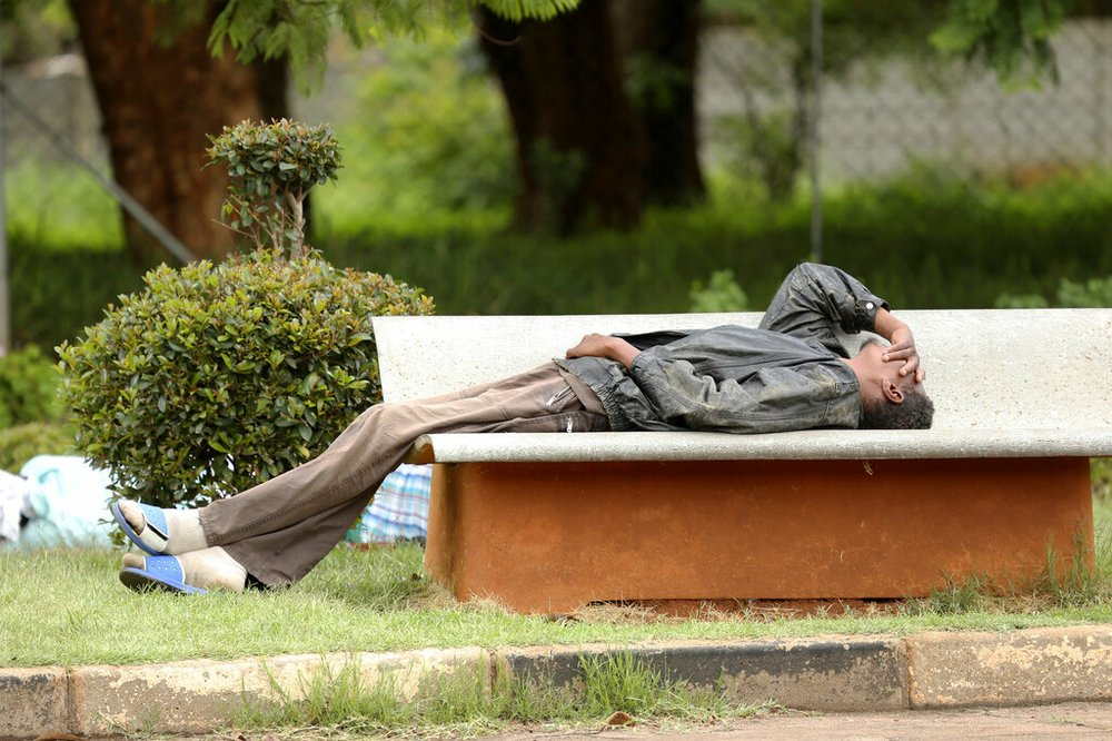 In this Jan. 9, 2019, photo, a man lies on a bench outside a government hospital after being turned away during the doctors strike at Parirenyatwa Hospital, in Harare, Zimbabwe. A doctors strike in Zimbabwe has crippled a health system that was already in intensive care from neglect. It mirrors the state of affairs in a country that was full of promise a year ago with the departure of longtime leader Robert Mugabe but now faces economic collapse.