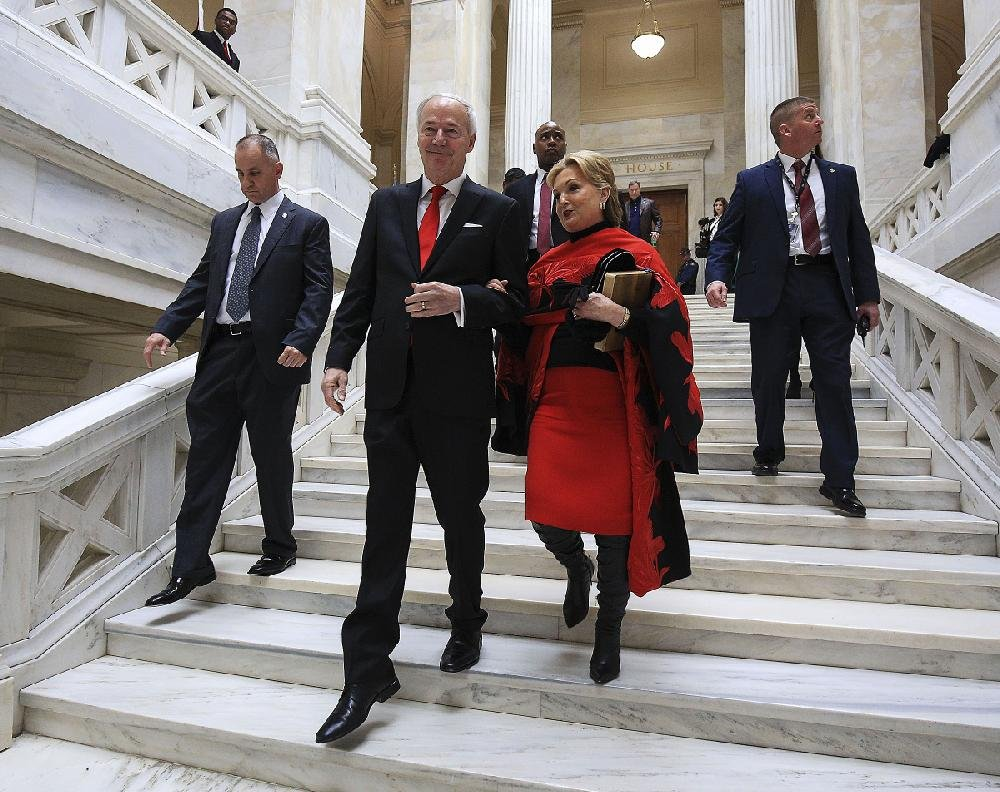 Gov. Asa Hutchinson and his wife leave the House chamber after his swearing-in.