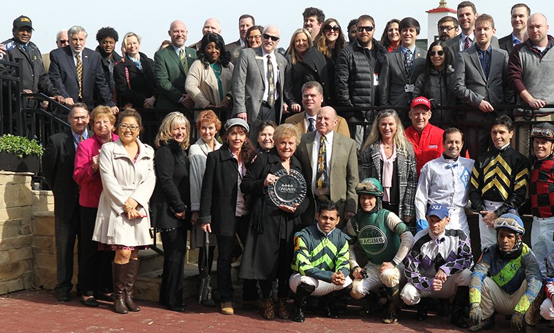 The Sentinel-Record/Richard Rasmussen WINNING CONNECTIONS: Jeannette Snyder, surrounded by her family and friends, as well as Oaklawn Park employees and jockeys, presents the trophy to the winning connections in the Larry Snyder Winner's Circle following the first race Friday at Oaklawn Park. Jeanette Snyder is the wife of legendary jockey and longtime Oaklawn steward Larry Snyder, who died in late October.