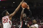 Georgia guard Tyree Crump (4) drives to the hoop past Arkansas defenders Gabe Osabuohien (22) and Keyshawn Embery-Simpson (11) during the second half of an NCAA college basketball game, Tuesday, Jan. 29, 2019 in Fayetteville. (AP Photo/Michael Woods)