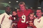Arkansas 2020 prospect Chris Vaughn (left) being held by his father and former Hog assistant Chris Vaughn  while posing with former Razorback quarterback Matt Jones.