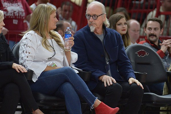 Johnny Mike Walker (right) sits with Mandy Macke, executive director of the Willard & Pat Walker Charitable Foundation, during a game between Arkansas and Texas State on Saturday, Dec. 22, 2018, in Fayetteville.