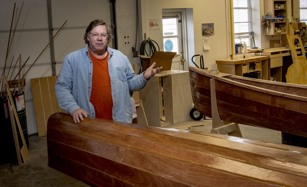 Greg Johnson stands with a canoe built during the January class taught at the Little Rock River Market. After a few finishing touches, it will go home with the father and son who built it.