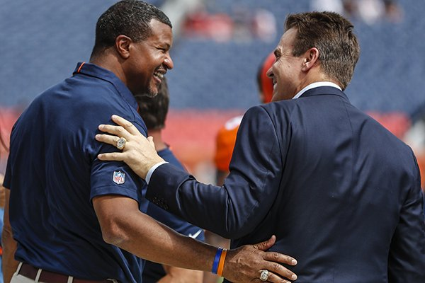 Former Denver Broncos defensive player Bill Romanowski talks with fellow former player Steve Atwater prior to an NFL football game against the Oakland Raiders, Sunday, Sept. 16, 2018, in Denver. (AP Photo/Jack Dempsey)