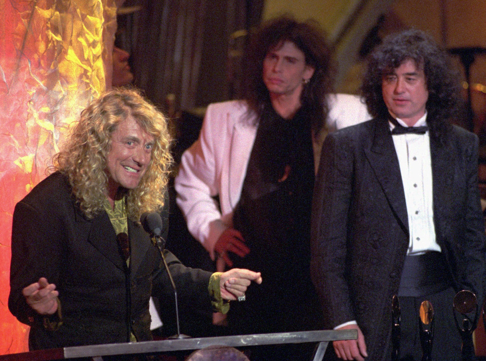 Robert Plant (left) speaks at Led Zeppelin's induction into the Rock and Roll Hall of Fame in 1995. The group's lead singer, Plant was joined onstage by guitarist Jimmy Page (right). Aerosmith's Steve Tyler is at center. (Democrat-Gazette file photo)