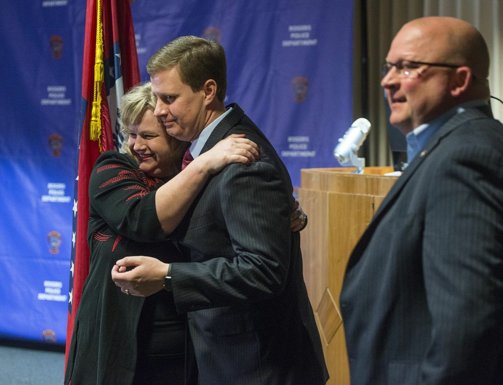 Amy Harrison hugs Nathan Smith, Benton County prosecutor, as Hayes Minor, Rogers chief of police looks on Thursday during a news conference at the Rogers Police Department. The conference was held following Grant Hardin pleading guilty to raping Harrison, at the time a teacher at Tillery Elementary School, in 1997.
