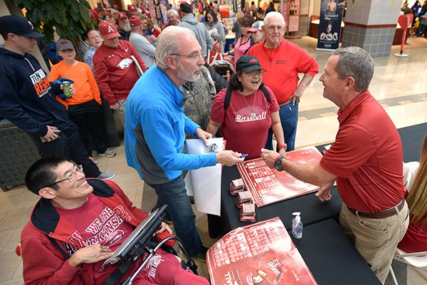 Arkansas fan David Petersen (left) of Springdale has a ticket from coach Dave Van Horn's 1,000th win autographed by Van Horn (right) Saturday, Feb. 3, 2018, during the Arkansas baseball team's annual fan day at the Northwest Arkansas Mall in Fayetteville.