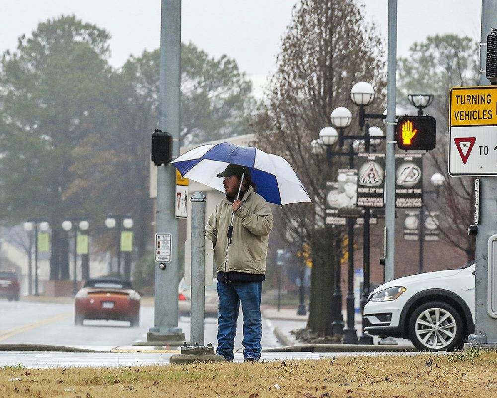 A pedestrian waits in the rain for a light to change before crossing a street in downtown North Little Rock on Monday morning.