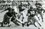 Arkansas back Henry Moore (30) runs during a game against Ole Miss on Saturday, Oct. 23, 1954, in Little Rock. George Walker (44) is shown watching the play from behind.