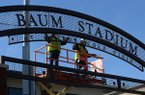 James Reeves (left) and Adam Murray, both workers with L&L Metal Fabrication in Tontitown work together Wednesday, Feb. 13, 2019, while taking measurements of signs over the several entrance gates for new lettering at the newly named Baum-Walker Stadium ahead of Friday's Opening Day. The name change was approved by university system trustees after the Willard & Pat Walker Charitable Foundation pledged $5 million toward the construction of an operations center that is projected to cost as much as $25 million.