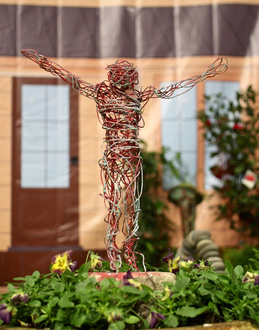 """Little Rock Land Design included this wire sculpture in the impromptu landscape it created in front of one of four vinyl """"house fronts"""" for the Landscape Challenge in Barton Coliseum during the 2018 Arkansas Flower and Garden Show on the Arkansas State Fairgrounds. Photo by Celia Storey"""