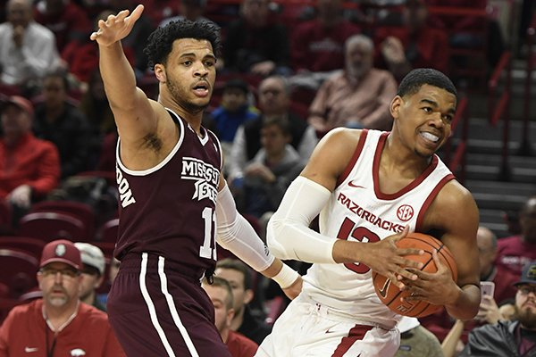 Arkansas guard Mason Jones (13) calls a timeout in front of Mississippi State defender Quinndary Weatherspoon during the first half of an NCAA college basketball game Saturday, Feb. 16, 2019, in Fayetteville. (AP Photo/Michael Woods)