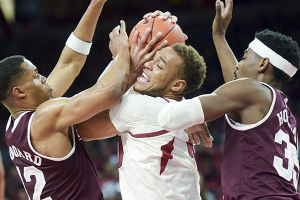 Arkansas forward Daniel Gafford is trapped by two Mississippi State defenders during a game Saturday, Feb. 16, 2019, in Fayetteville.