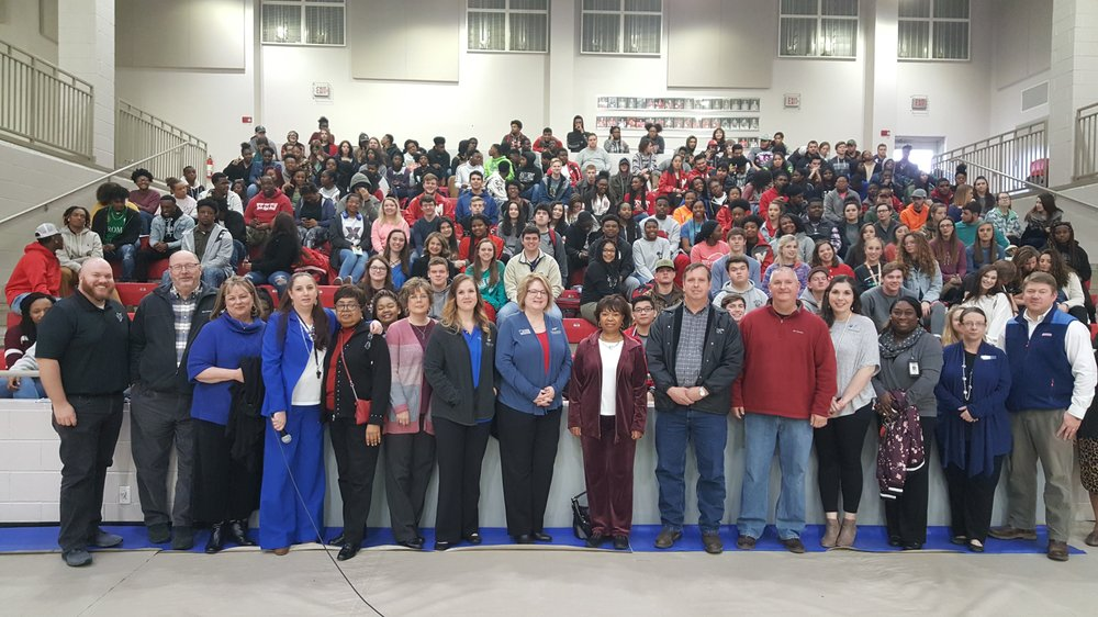 Local professionals and seminar leaders stand in front of the 2019 Magnolia High School class after Wednesday's financial planning program.