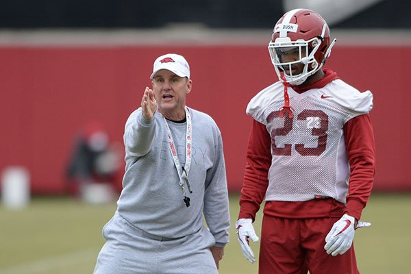 Arkansas coach Chad Morris (left) instructs freshman defensive back Devin Bush during a practice Friday, March 1, 2019, in Fayetteville.