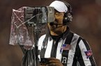 In this Nov. 3, 2018, file photo, referee Reggie Smith reviews a targeting penalty during the first half of an NCAA college football game between Oklahoma and Texas Tech, in Lubbock, Texas. (AP Photo/Brad Tollefson, File)