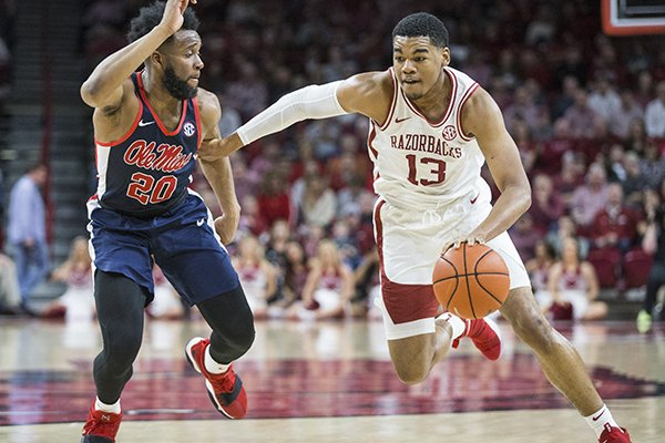 Arkansas guard Mason Jones (13) drives around Ole Miss guard D.C. Davis (20) during a game Saturday, March 2, 2019, in Fayetteville.