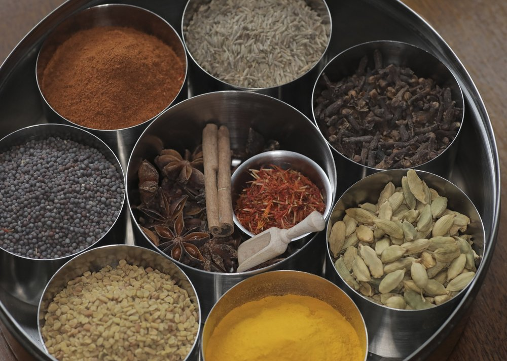 A basic Indian spice box includes (clockwise from top) cumin seeds, whole cloves, green cardamom pods, turmeric, fenugreek seeds, black mustard seeds and Indian red chile as well as star anise, saffron and cinnamon (center).  Photo by John Sykes Jr.