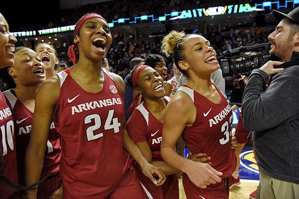 Arkansas' Chelsea Dungee, right, Malica Monk, center, and Taylah Thomas join teammates in celebrating a 95-89 win over South Carolina in an NCAA college basketball game in the Southeastern Conference women's tournament Friday, March 8, 2019, in Greenville, S.C. (AP Photo/Richard Shiro)