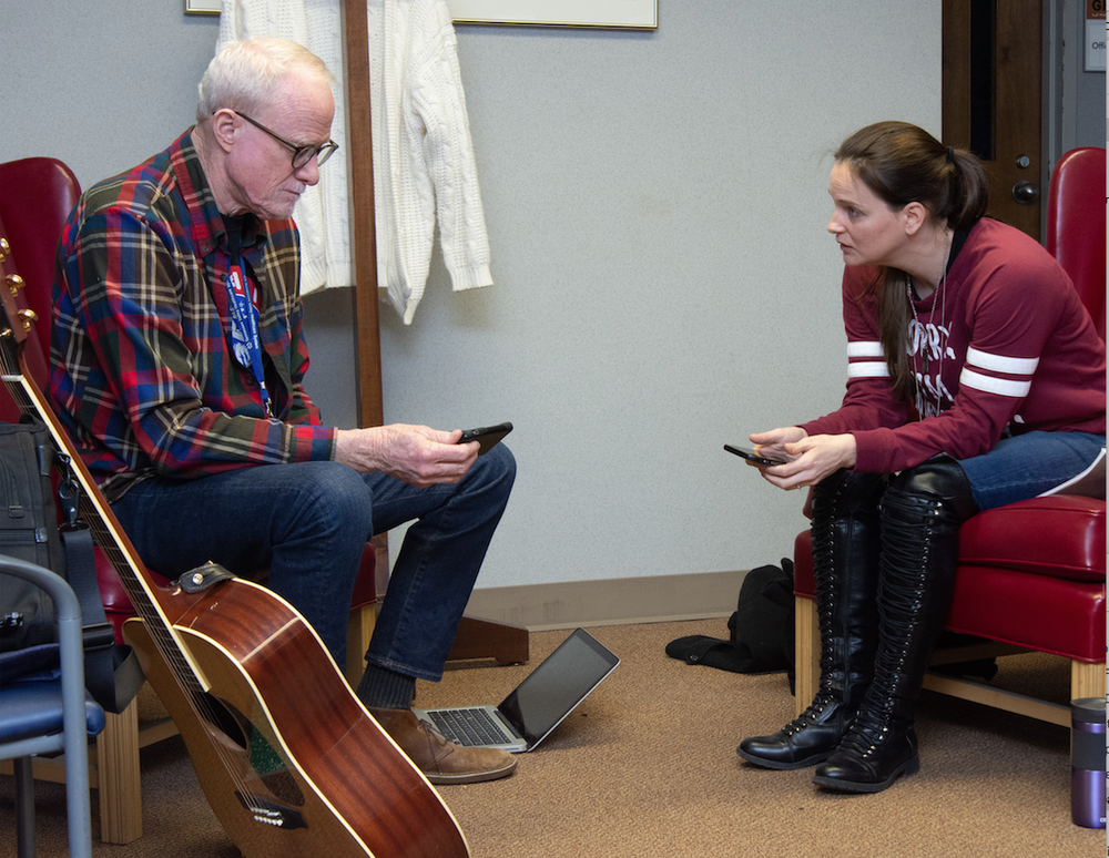 Songwriter and Operation Song founder Bob Regan and veteran Lesa Dickson of Mayflower listen to different types of music, trying to find a style for a song that chronicles Dickson's story. (Arkansas Democrat-Gazette/CARY JENKINS)