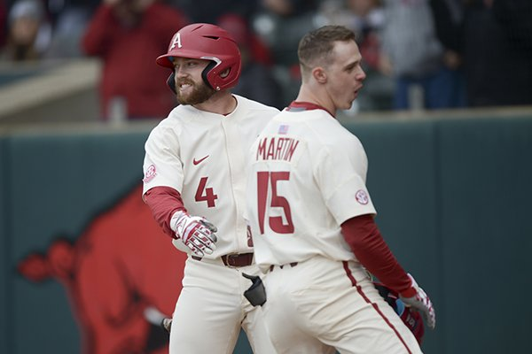 Arkansas infielders Trevor Ezell (4) and Casey Martin celebrate after Martin hit a home run during a game against Louisiana Tech on Sunday, March 10, 2019, in Fayetteville.