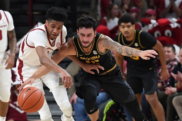Arkansas' Isaiah Joe and Missouri's Jordan Geist struggle for the ball Wednesday Jan. 23, 2019 at Bud Walton Arena in Fayetteville.