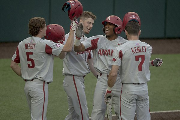 Arkansas outfielder Christian Franklin (25) celebrates a grand slam with infielder Jacob Nesbit (5) during an NCAA college baseball game against Texas, Tuesday, March 19, 2019, in Austin, Texas. (Nick Wagner/Austin American-Statesman via AP)