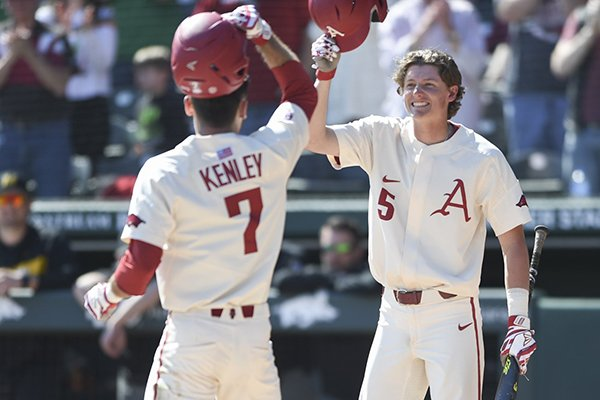 Arkansas third baseman Jacob Nesbit (5) greets second baseman Jack Kenley (7) after Kenley hit a home run during a game against Missouri on Sunday, March 17, 2019, in Fayetteville.