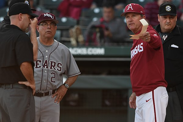 Arkansas coach Dave Van Horn (right) and Missouri State coach Keith Guttin (left) meet with umpires prior to a game Tuesday, April 17, 2018, in Fayetteville.