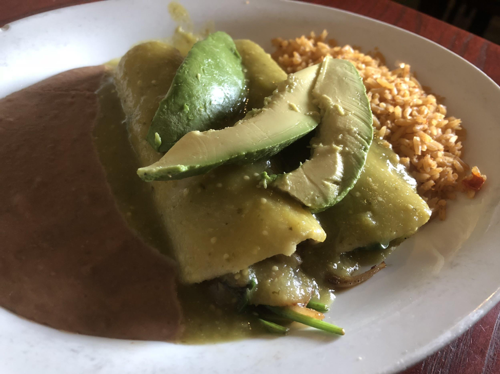 "The ""Enchiladas Alejandra"" features two vegetable enchiladas, stuffed with sauteed onions and bell peppers, drenched in salsa verde and topped with avocado slices."