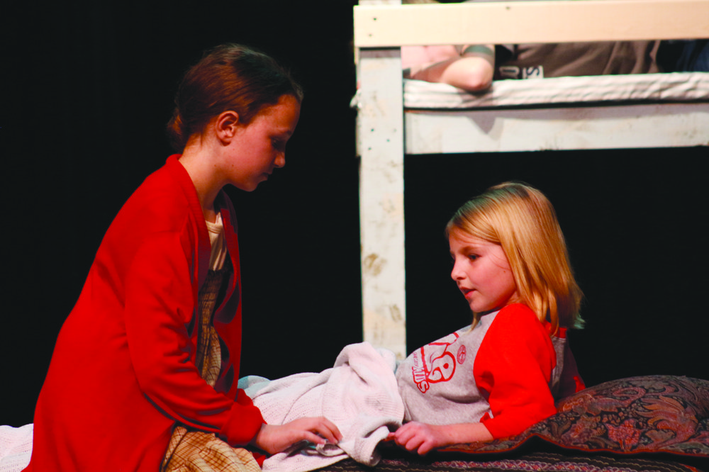 "Maryana Woolen, playing Annie, talks with Braelyn Allen, playing one of the orphans who wakes up crying out for her mommy, during a rehearsal of ""Annie KIDS."""