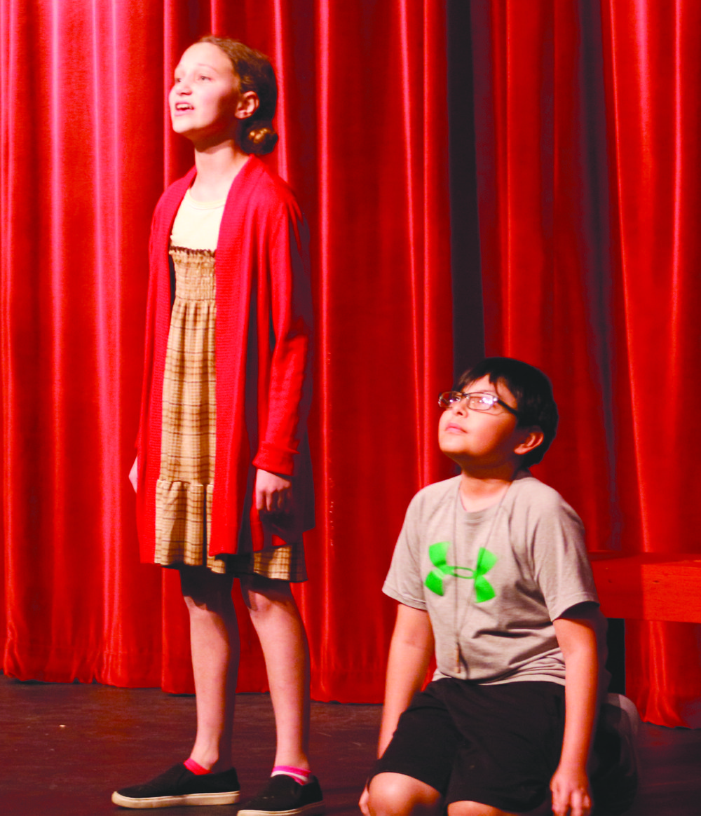 "Maryana Woolen, playing Annie, stands with David Valero, playing the dog Sandy, during a rehearsal of ""Annie KIDS"" while singing the well-known song ""Tomorrow."""