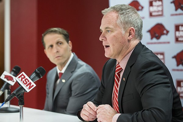 Arkansas athletics director Hunter Yurachek (foreground) answers a question while basketball coach Eric Musselman looks on during a news conference Monday April 8, 2019, in Fayetteville.