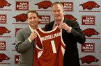 Arkansas basketball coach Eric Musselman (left) and Arkansas athletics director Hunter Yurachek hold up a jersey prior to a news conference Monday, April 8, 2019, at Bud Walton Arena in Fayetteville.