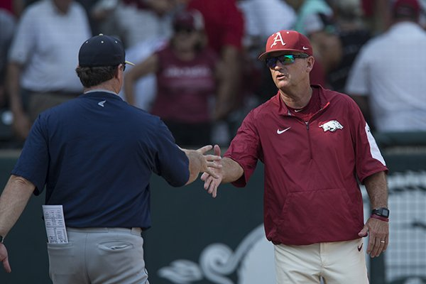 Arkansas coach Dave Van Horn (facing) shakes hands with Oral Roberts coach Ryan Folmar following an NCAA regional game Friday, June 1, 2018, in Fayetteville.