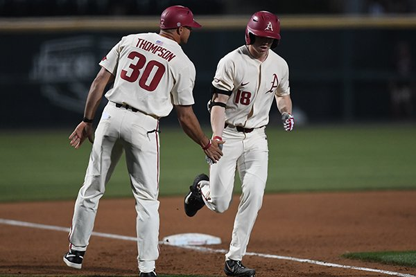 Arkansas outfielder Heston Kjerstad (right) is congratulated by hitting coach Nate Thompson after Kjerstad hit a grand slam home run during the fourth inning of a game against Oral Roberts on Tuesday, April 9, 2019, in Fayetteville.