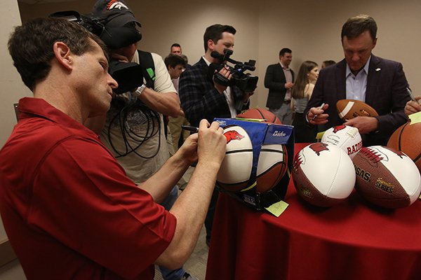 Arkansas basketball coach Eric Musselman (left) and football coach Chad Morris (right) sign balls before the State of the Hog event on Wednesday, April 10, 2019, at Verizon Arena in North Little Rock.