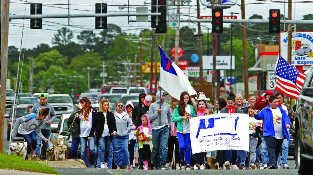 Walk of faith: Banners waving, a group makes their way down North West Avenue during the fifth annual Walk for Christ on Sunday. The event began at the Northwest Shopping Village Shopping Center and ended at the Boys and Girls Club of El Dorado.