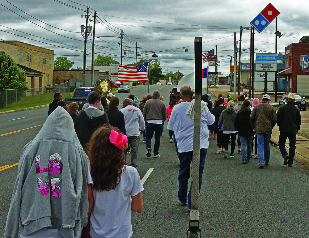 Walk: Banners waving, a group makes their way down North West Avenue during the fifth annual Walk for Christ on Sunday. The event began at the Northwest Shopping Village Shopping Center and ended at the Boys and Girls Club of El Dorado.