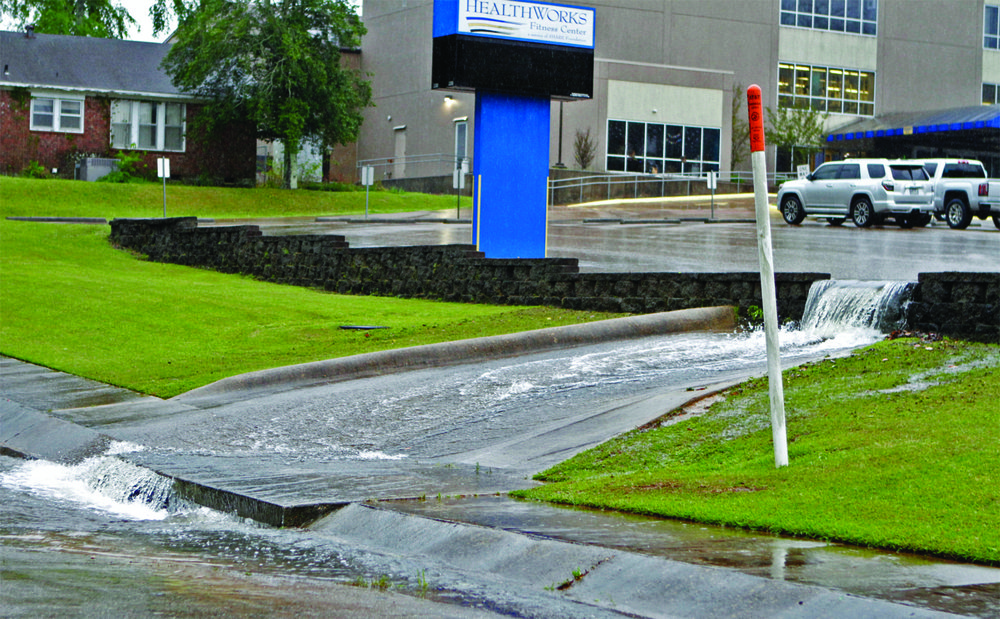 Waterfall: Water pours out of the HealthWorks Fitness Center parking lot onto North Madison on Saturday.