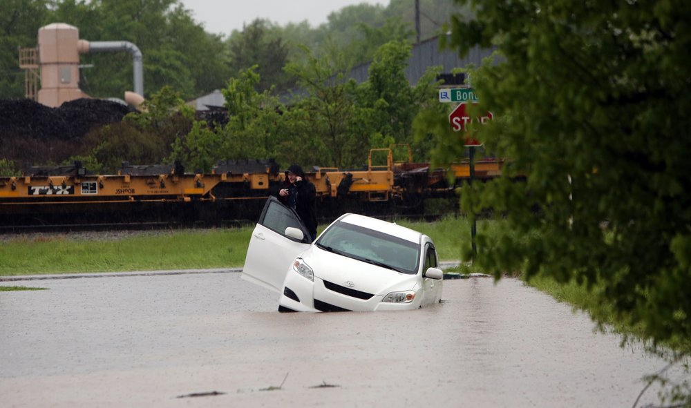 A motorist talks on a cellphone from a stranded car at the intersection of 12th Street and Bond Street in east Little Rock on Thursday morning.