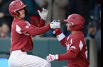 Arkansas shortstop Casey Martin (left) and outfielder Dominic Fletcher celebrate after Martin hit a grand slam during a game against Mississippi State on Friday, April 19, 2019, in Fayetteville.
